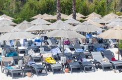 Camas e guarda-chuvas de Sun na praia com areia branca Imagem de Stock Royalty Free