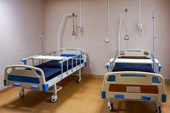 Camas para los pacientes en la sala de hospital imagen de archivo