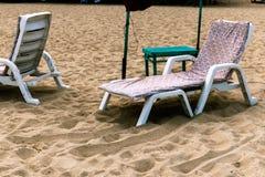 Camas y paraguas coloridos en una playa tropical imagen de archivo