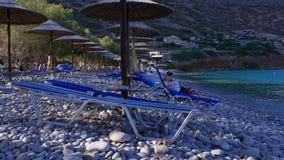 Camas y paraguas de Sun en la playa de la grava, Creta almacen de video