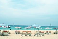 Camas y paraguas en una playa Imagen de archivo