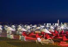 Camas y Straw Umbrellas On una playa en la noche Imagen de archivo