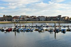 Small fishing village with pier and boats. Beach, harbour and promenade with trees. Sunset light, blue sky with clouds. Cambados, stock photos