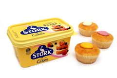 Camberley, UK - Feb 22nd 2017: A tub of Stork Cakes margarine, w. Ith three cupcakes or fairy cakes. Stork has been an iconic brand in the UK since 1920. White Royalty Free Stock Images