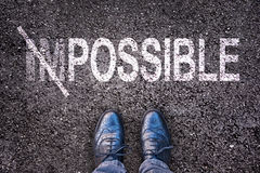 Cambiando la palabra imposible en posible en un camino con los pies foto de archivo libre de regalías