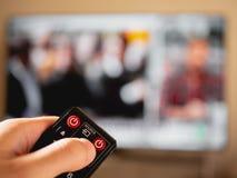 Cambie el canal en la televisión con teledirigido foto de archivo libre de regalías