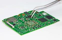 Cambio de un procesador en una placa de circuito electrónica Fotos de archivo libres de regalías