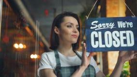 Cambio joven atractivo de la camarera cerrado abrir la muestra en la sonrisa de la puerta del café almacen de video