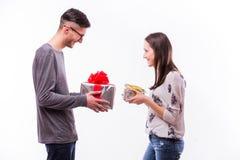 Cambio joven feliz de los pares del inconformista con el presente que aisló en un fondo blanco Foto de archivo libre de regalías