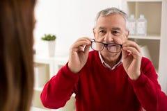 Cambio paciente del aftere de los vidrios de las tomas del hombre mayor de la dioptría fotografía de archivo libre de regalías