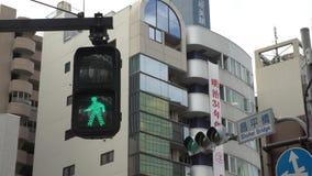 cambio peatonal del tráfico de ciudad de Tokio de la muestra del paso de peatones 4K rojo al color verde metrajes