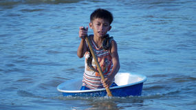 Cambodian boy (with snake) paddling in a basin Royalty Free Stock Photography