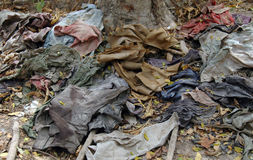 Cambodia Killing Fields - Victims Clothes. The clothing of the Khmer Rouge victims still lies in piles scattered around the the Killing Fields near Phnom Penh Stock Photography
