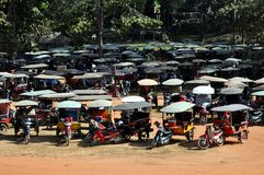 Cambodia - Rickshaws parking. December 2012 - Siem Reap, Angkor Wat area (Cambodia) - Rickshaws parking with hundrends of tuc tuc waiting for clients after the Stock Photography