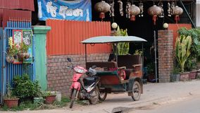 Little Asian girl sits in a moto rickshaw near a house with red lanterns. Cambodia, Siem Reap 12/08/2018 a little Asian girl sits in a moto rickshaw near a house stock photo