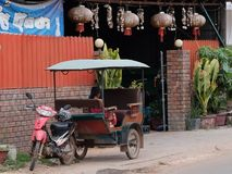 Little Asian girl sits in a moto rickshaw near a house with red lanterns stock photography