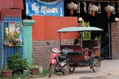 Little Asian girl sits in a moto rickshaw near a house with red lanterns. Cambodia, Siem Reap 12/08/2018 a little Asian girl sits in a moto rickshaw near a house stock images