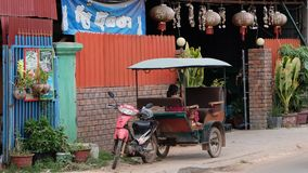 Little Asian girl sits in a moto rickshaw near a house with red lanterns. Cambodia, Siem Reap 12/08/2018 a little Asian girl sits in a moto rickshaw near a house royalty free stock photos