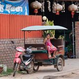 A little Asian girl sits in a moto rickshaw near a house with red lanterns. Cambodia, Siem Reap 12/08/2018 a little Asian girl sits in a moto rickshaw near a royalty free stock photo