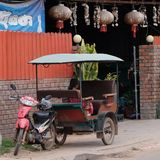 A little Asian girl sits in a moto rickshaw near a house with red lanterns. Cambodia, Siem Reap 12/08/2018 a little Asian girl sits in a moto rickshaw near a stock photography