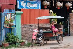 A little Asian girl sits in a moto rickshaw near a house with red lanterns. Cambodia, Siem Reap 12/08/2018 a little Asian girl sits in a moto rickshaw near a stock images