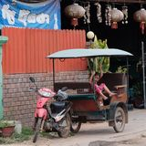Little Asian girl sits in a moto rickshaw near a house with red lanterns. Cambodia, Siem Reap 12/08/2018 a little Asian girl sits in a moto rickshaw near a house royalty free stock photography