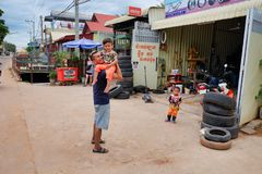 Cambodia, Siem Reap 12/08/2018 a man with a child in his arms near the tire shop, slums of Asia, residents of poor areas of the royalty free stock photography