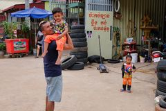 Man with a child in his arms near the tire shop, slums of Asia, residents of poor areas of the. Cambodia, Siem Reap 12/08/2018 a man with a child in his arms stock image