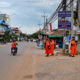 Several Buddhist monks in orange clothes stand on the side of the road, several scooters ride along stock images