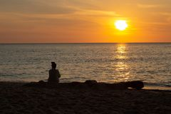 Cambodian Asian Woman Watching the Sunset & Boat by the Ocean. Cambodian Khmer girl sitting peacefully watching the beautiful golden sunset across the ocean stock photo