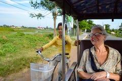 Cambodian boy on bicycle gets a free ride with tuk tuk. Kampong Cham, Cambodia - November 20, 2014: Cambodian boy on bicycle getting a free ride from tuk tuk Royalty Free Stock Photo