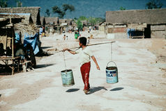 Cambodian boy carrying water buckets Royalty Free Stock Photo