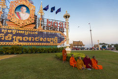 Cambodian Buddhist monks sitting on the grass in front of the Pa. Group of Cambodian Buddhist monks sitting on the grass in front of the monument dedicated to Royalty Free Stock Image