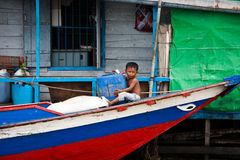 Cambodian child sits on front of boat Royalty Free Stock Images