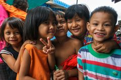 Cambodian children in a fishing village. SIHANOUKVILLE, CAMBODIA - 7/20/2015: A group of children play in the streets of their fishing village Stock Photos
