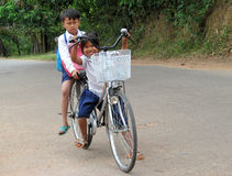 Cambodian children going to school by bycicle. Cambodian children with books and bags going to school by bycicle, People living in Cambodia. South east Asia Stock Photo