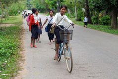 Cambodian children going to school by bycicle. Cambodian children with books and bags going to school by bycicle, People living in Cambodia. South east Asia Stock Photos