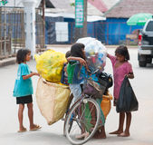 Cambodian children have to work. SIEM REAP, CAMBODIA - JUNE 28, 2014: Four local unidentified girls of school age arrange large bags with different kinds of Royalty Free Stock Photo
