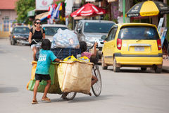 Cambodian children have to work. SIEM REAP, CAMBODIA - JUNE 28, 2014: Four local unidentified girls of school age carry large bags with different kinds of trash Royalty Free Stock Photos
