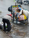 Cambodian children in trash cart. PHNOM PENH, CAMBODIA - JULY 3, 2014: An unidentified senior dustwoman picks recyclable trash by her cart where two children sit Stock Image
