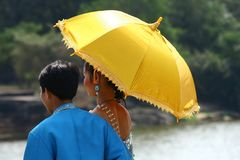Cambodian couple under yellow umbrella Royalty Free Stock Images