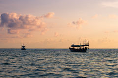 Small Asian Boats on the Ocean at Sunset Royalty Free Stock Photography