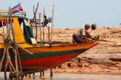 Cambodian floating village boat construction with kids playing. In the mud Stock Images
