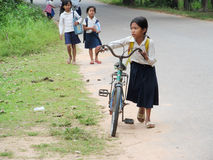 Cambodian girl with bycicle going to school. Cambodian children girl with books and bycicle going to school, People living in Cambodia. South east Asia Stock Photo