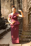 Cambodian Girl in Dancing in Khmer Dress in Ancient Building of Angkor City. A Cambodian girl dancing in a traditional Khmer dress at Ta Prohm Royalty Free Stock Photo