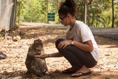 Asian Girl Feeding a Monkey Peanuts Stock Photos