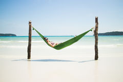 Happy Asian Girl in a Hammock on a Tropical Island Beach stock image