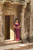 Cambodian Girl in Khmer Dress by Doorway of  Ancient Building of Angkor City Royalty Free Stock Photo