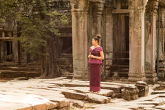 Cambodian Girl in Khmer Dress at Entrance to Ta Prohm, Angkor City. A Cambodian girl in a traditional Khmer dress stands by an ancient doorway at Ta Prohm Royalty Free Stock Image