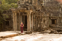 Cambodian Girl in Khmer Dress at Entrance to Ta Prohm, Angkor City. A Cambodian girl in a traditional Khmer dress stands by an ancient doorway at Ta Prohm Stock Photo